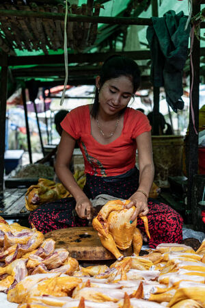 Woman cutting poultry meat in crossed-leg position