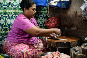 Woman removing scale in market