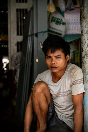 Young man sitting at entrance of market