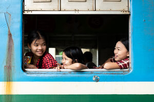 Three girls sitting by car window