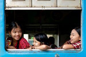 列車の窓辺に腰掛けた三人の女の子