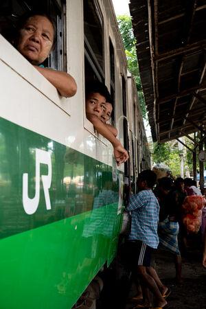 ダニンゴン駅に停まっている列車の窓から顔を出す乗客