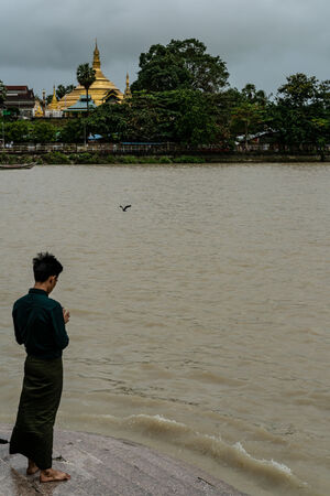Man throwing offerings into river