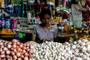 Woman working on the other side of pile of garlic