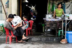 屋台で新聞を読む男