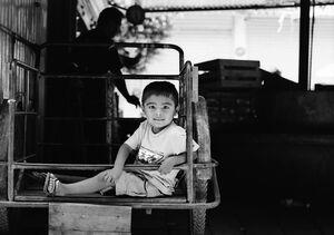 荷車の上で足を伸ばす男の子