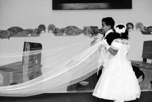 Kids holding hemline of wedding dress