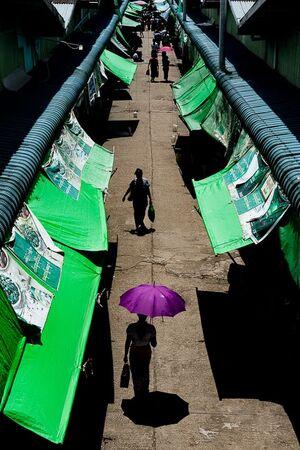 市場の通路を歩く紫の傘を差した女性