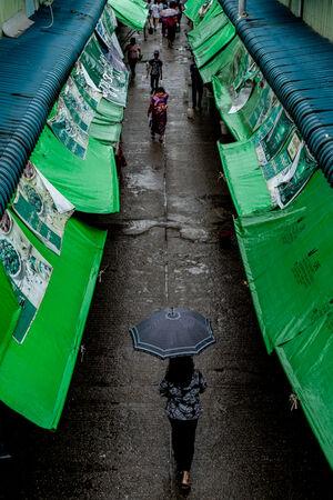 傘を差して通路を歩く女性