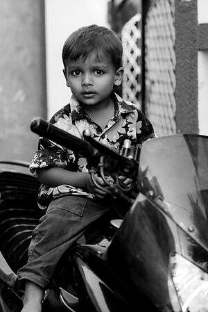Boy climbing on motorbike