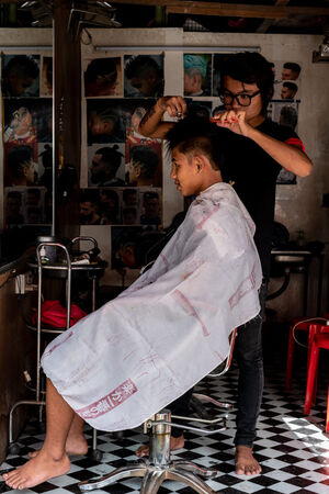 Bespectacled barber cutting hair