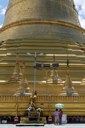 Women standing under same umbrella in front of Shwemawdaw Pagoda