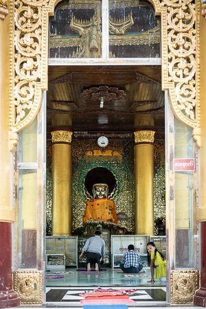 壁時計の下の仏像