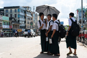 Schoolboys waiting for bus by roadside