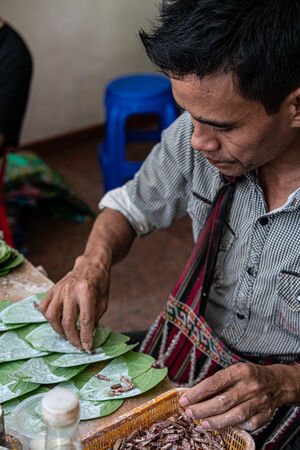 Man putting betel nuts on betel leaves