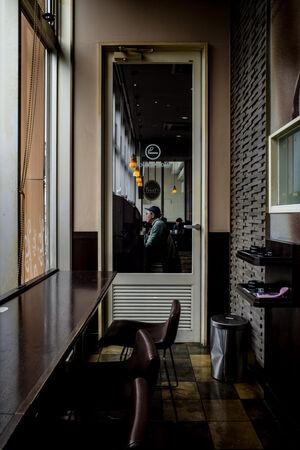 ガラス張りのドアの向こうに腰を下ろした年配の男性