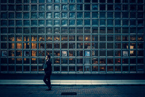 Businessman walking in front of glassed wall