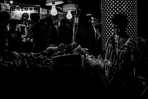 Older woman selling fruits in Linjiang Night Market