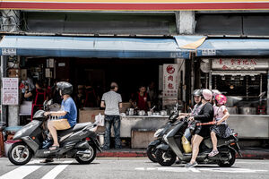Motorbikes waiting at traffic light in front of shop