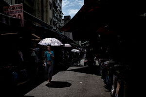 Older woman walking with umbrella near Bailan Market