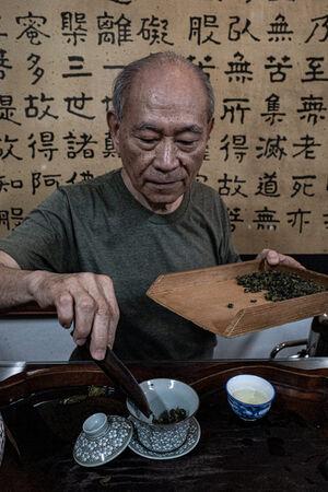 カップの中に茶葉を入れる男