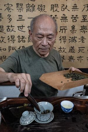 Man setting tea leaves in cup