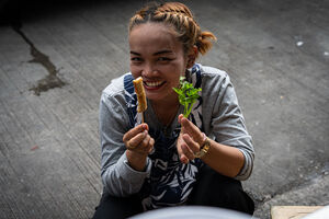 Woman with skewer and coriander