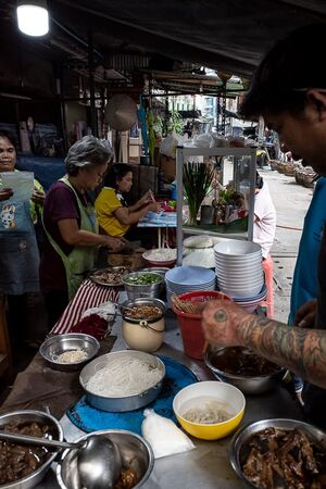 Tattoed man working in food stall