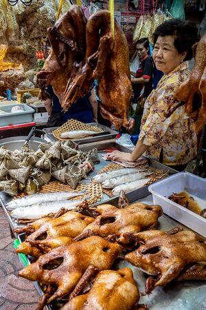 女性の前に並べられた丸焼きのチキンと魚とちまき