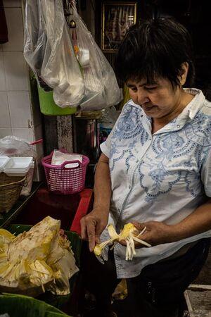 大きな果物を剥く女性