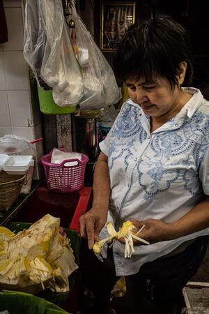 Woman peeling a big fruit