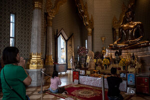 Woman praying in Wat Trimit