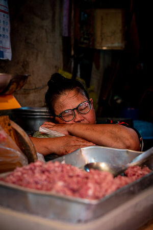Female butcher taking a nap in Khlong Toei Market