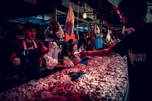 Man buying meat in a butcher in Khlong Toei Market