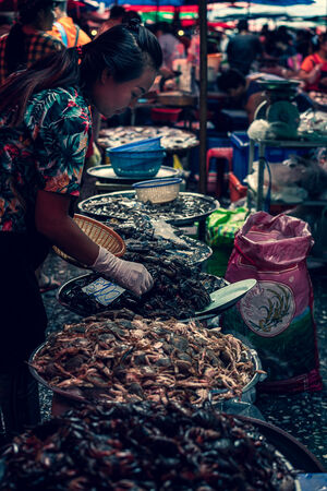 Woman selling crabs and shrimps in Khlong Toei Market