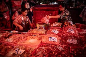 Two women working together in a butcher in Khlong Toei Market