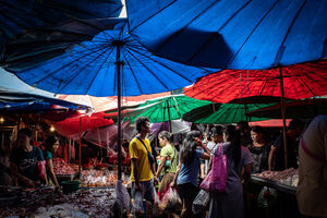 Shoppers wriggling under colorful parasols in Khlong Toei Market
