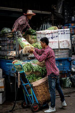 クロントゥーイ市場でトラックから野菜を下ろしていたふたりの男