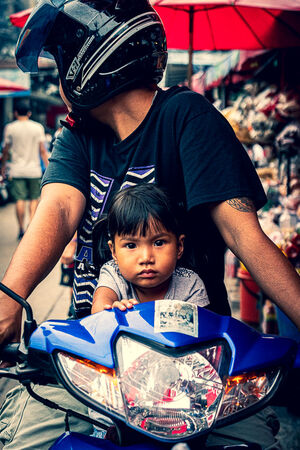 Little girl riding a motorbike with her father