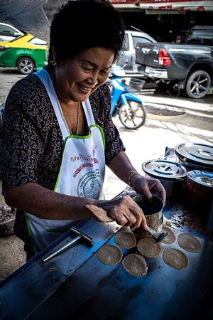 Woman cooking Khanom Bueang in a food stall