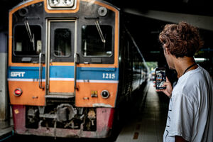 Man making a video of Maeklong Railway