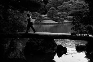 Man walking on stone bridge