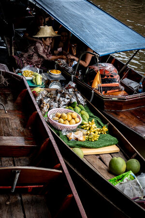 Vendor on a boat selling fruits to tourists on another boat
