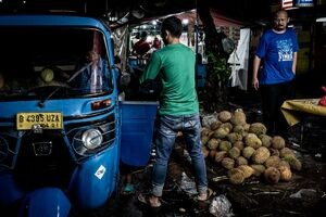 Men loading durians onto Bajaj