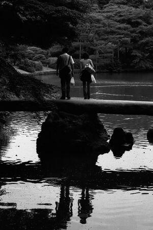 Couple stopping on stone bridge
