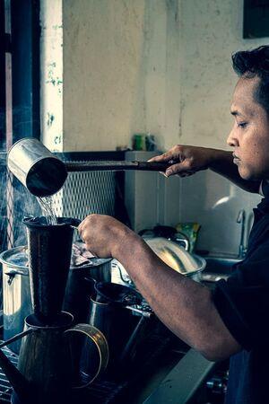 ネルドリップでコーヒーを淹れる男