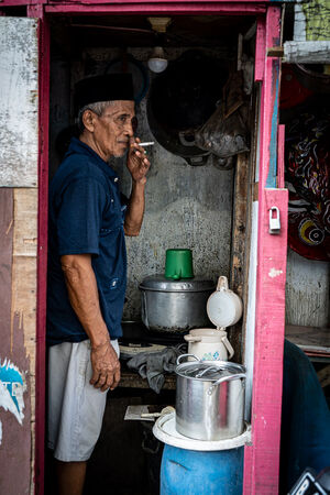 Man with a cap called Songkok smoking a cigarette in the hut