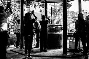 Silhouetted people praying around the incense burner in Jin De Yuan