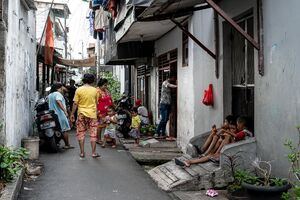 People hanging out in the narrow lane in the residential area