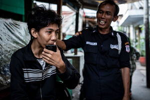 Two men standing talking in the residential area in Jakarta